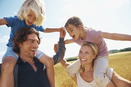 A mother and father smiling happily with their children balancing on their shoulders in a wheat field